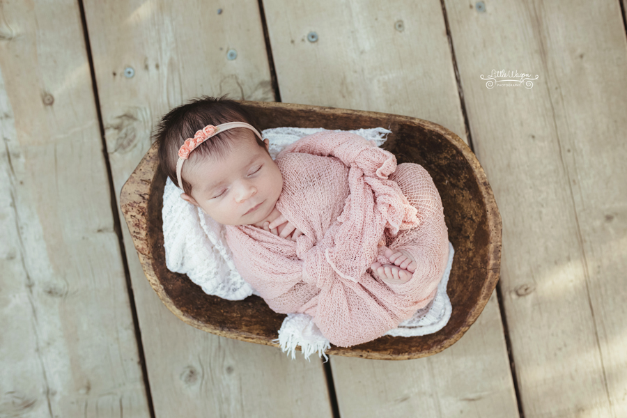 baby girl wrapped in pink swaddle.